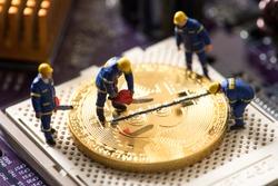 miniature worker cutting bitcoin , halving concept