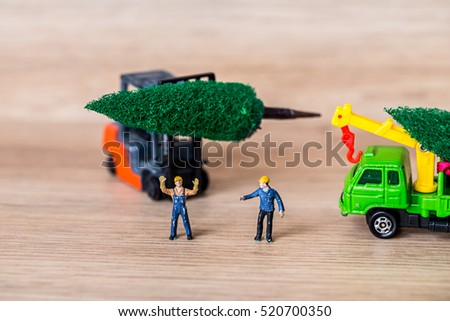Photo of Miniature Worker Passenger Christmas Tree by Truck on Wooden floor ,Determined Image for Christmas Holiday and Happy New Year Gift Celebration concept.