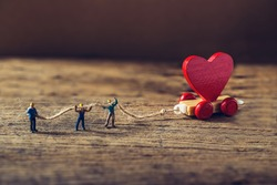 Miniature worker try to tow red heart shape of wooden toy train on grunge wooden floor,Image for team building or love valentine day concept.