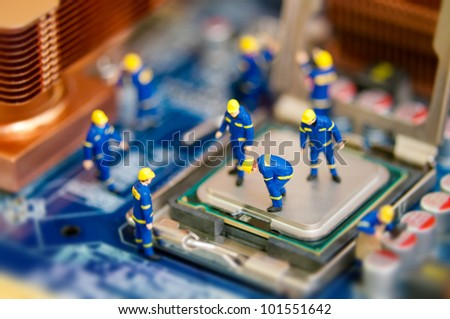 Miniature workers repairing computer motherboard - stock photo