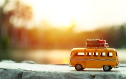 Miniature yellow van on the road with summer scene