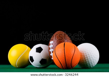 Miniaturized sport balls over black background. Shallow depth of field. Focus is on the front.