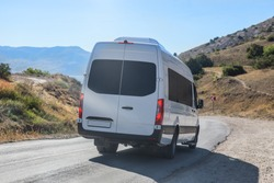 Minibus Moves along the Mountain Winding Road to the Sea in summer