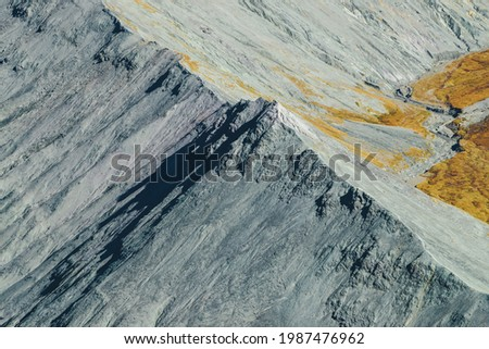 Minimal autumn landscape with gray rocky pointy peak in sunshine. Spectacular scenic view from above to sharp mountain ridge in fall time. Minimalist mountain scenery with rockies and autumn colors. Stockfoto ©