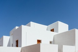 Minimal buildings background with traditional Greek style architecture. Low angle view of white houses against a blue clear summer sky. Outdoor estate construction of modern residential building.