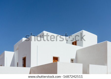 Minimal buildings background with traditional Greek style architecture. Low angle view of white houses against a blue clear summer sky. Outdoor estate construction of modern residential building.  Foto stock ©