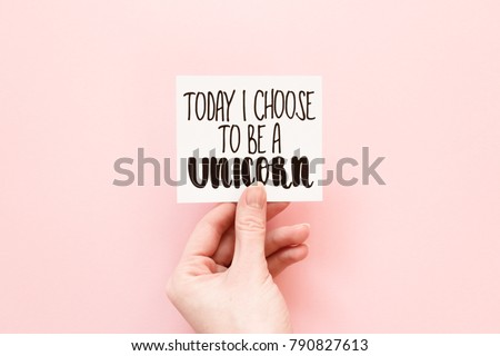 """Minimal composition on a pale pink pastel background with girl's hand holding card with handwritten quote """"today i choose to be a unicorn"""""""