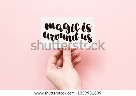 Minimal composition on a pink pastel background with girl's hand holding card with quote - Magis is around us #1059951839