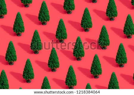 Minimal composition pattern background of green Christmas trees on pastel red. New Year concept.