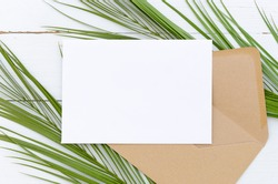 Minimal composition white blank card and envelope on palm leaves on a white wooden background. Mockup with envelope and blank card. Flat lay. Top view.