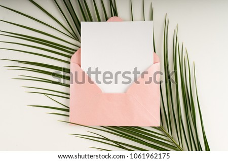 Minimal composition with a pink envelope, white blank card and a palm leaf on a white background. Mockup with envelope and blank card. Flat lay. Top view. #1061962175