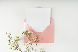 Minimal composition with a pink envelope, white blank card and a wax flower on a white background. Mockup with envelope and blank card. Flat lay. Top view.