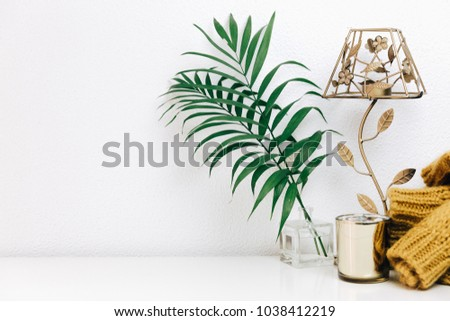 Minimal composition with green tropical leaves, candle and trendy warm sweater. Nordic decorations, Scandinavian style interior  #1038412219