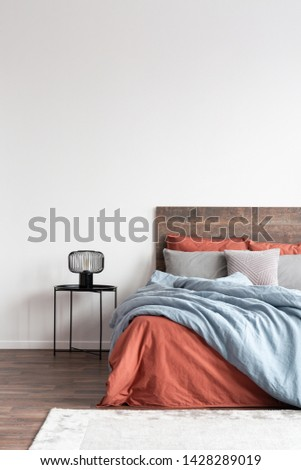 Minimal cozy interior with wooden bed with natural bedclothes on the empty white wall #1428289019