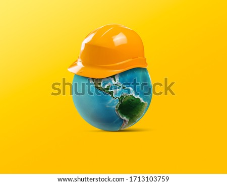 Minimal design for May first International Workers Day. International labor day design helmet and world together on the yellow background.