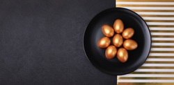 Minimal easter banner. Stylish Easter golden decorated eggs on black plate isolated on black marble background. Flat lay trendy easter. Happy Easter card with copy space for text.