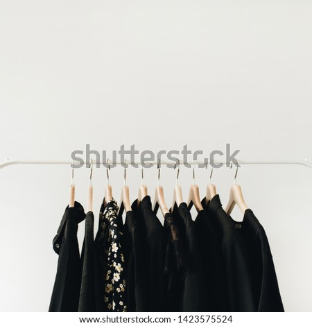 Minimal fashion clothes concept. Black female blouses and t-shirts on hanger on white background.