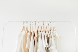Minimal fashion clothes concept. Female blouses and t-shirts on hanger on white background. Fashion blog, website, social media hero header.