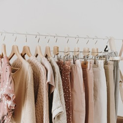 Minimal fashion clothes concept. Stylish female blouses, sweaters, pants, jeans and t-shirts on hanger on white background. Fashion blog, website, social media hero header.