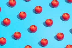 Minimal flat lay food texture. Summer abstract trendy fresh concept. red Apple pattern on bright light blue background, copy space.