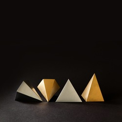 Minimal geometry still life composition. Platonic solids figures geometry. Abstract gold and silver color geometrical figures. Three-dimensional pyramid objects on black background.
