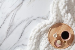 Minimal home workspace with diary, pen, cup of coffee, milk, french macaron and cozy snow white knit cotton plaid. Handmade merino wool chunky knit warm blanket. Flat lay, top view. Organic cotton.