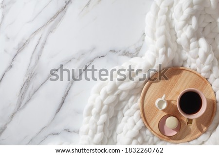 Minimal home workspace with diary, pen, cup of coffee, milk, french macaron and cozy snow white knit cotton plaid. Handmade merino wool chunky knit warm blanket. Flat lay, top view. Organic cotton. Сток-фото ©
