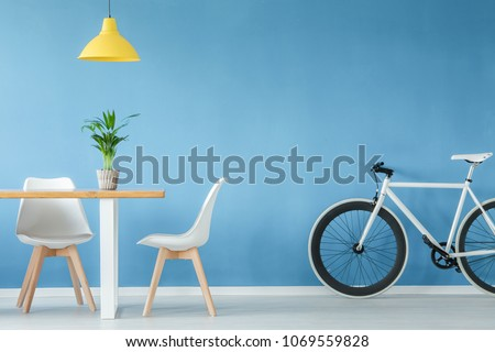 Minimal, modern interior with two chairs, a bicycle, a table with a plant on it and a yellow lamp above, against blue wall #1069559828