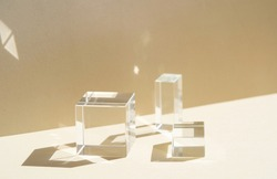 Minimal modern product glass display on textured background in neutral earth tones with shadows