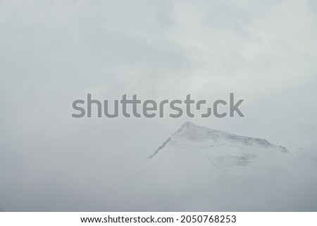 Minimal mountain landscape with high pointy rock in clouds. Minimalist mountain scenery with sharp snowy mountain peak over clouds. Snow-white pointed pinnacle above white clouds. Big top in dense fog Photo stock ©