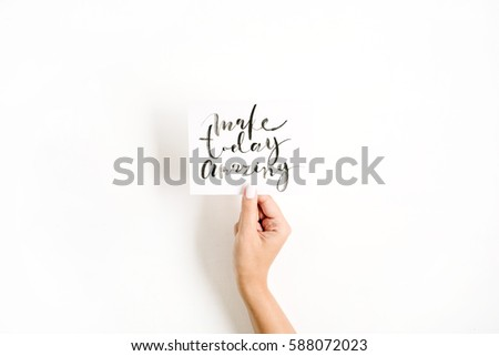 Minimal pale composition with girl's hand holding card with quote Make Today Amazing written in calligraphic style on paper on white background. Flat lay, top view #588072023