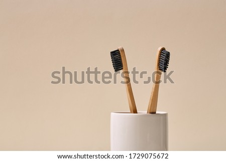 Photo of Minimal picture of two bamboo toothbrushes isolated on beige nude background. Picture banner eco friendly products with copyspace, text. Healthcare concept plastic free. Organic, sensitive, protection