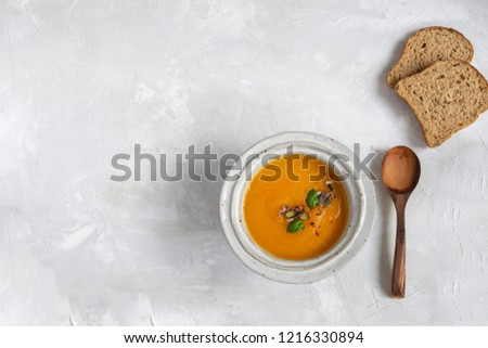 Minimal picture - pumpkin soup plate with bread and wooden spoon. Top view, gray background, copy space.