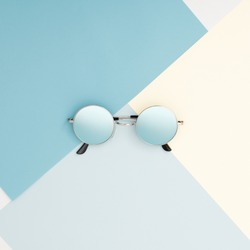 Minimal style. Minimalist Fashion photography. Fashion summer is coming concept. Blue glasses on a blue background, top view. Trendy minimal style with colorful paper backdrop