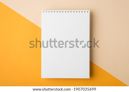 Minimal style note pad. Above overhead close up flat lay photo of clear spiral notepad with copy place for design isolated half yellow and beige backdrop desktop Сток-фото ©