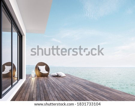 Minimal style room terrace with sea view 3d render,There has dark wooden floors,decorated with rattan furniture and white lantern ,overlooking the sea and sky.