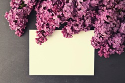 Minimal vintage flower composition, bunch of purple lilac blossoms on black table top background. Valentine, International Women, mother day present, easter greeting. Copy space, close up, top view.