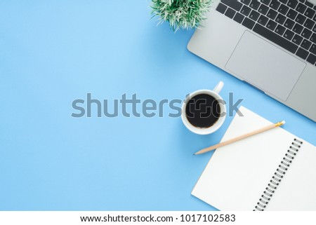 Minimal work space - Creative flat lay photo of workspace desk. Top view office desk with laptop, notebooks and coffee cup on blue color background. Top view with copy space, flat lay photography. Сток-фото ©