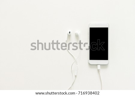Minimal work space - Creative flat lay photo of workspace desk with earphones and mobile phone with blank screen on copy space white background. Top view mock up , flat lay photography.