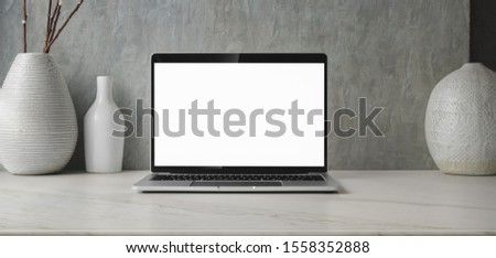 Minimal workspace with blank screen laptop computer and ceramic vase decorations with copy space  #1558352888