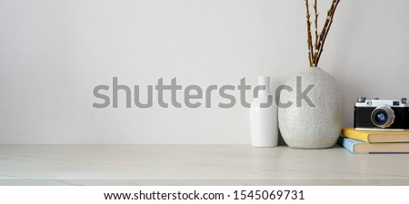 Minimal workspace with copy space, camera and office supplies on white desk and white wall background  #1545069731