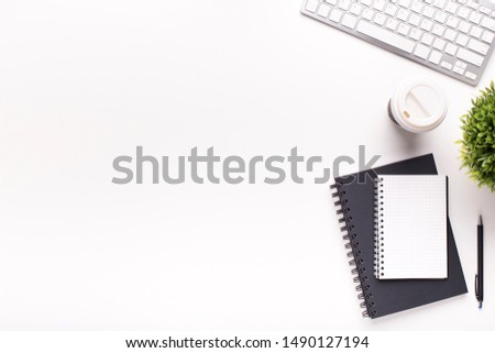 Minimalism concept. Black and white notepads, keyboard and plant on office table with free space for advertisement