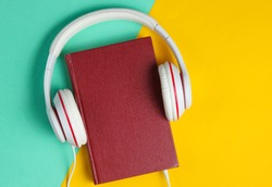 Minimalism online listen to books concept. Audiobook Book with headphones on colored background. Top view