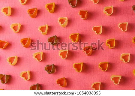 Minimalism style. Repetition concept. View from above on pasta pattern with heart shape, on colored background.  #1054036055