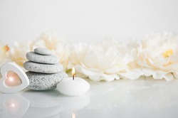 Minimalist balance zen stone beauty products background with wooden heart light, spa candle burning and nice reflection. Advertisement tender delight background copy space concept.
