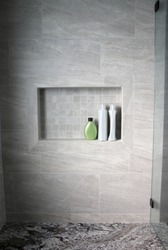 minimalist bathroom shower with gray tile and niche shelf with shampoo bottles and granite bench