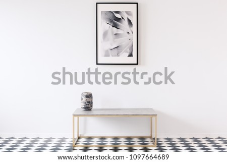Minimalist black and white apartment interior for an artist with a luxurious golden bench and a framed picture on an empty wall