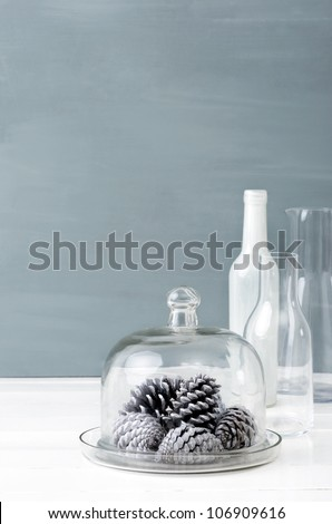 Minimalist christmas interior decoration with clear glass bottles, white pine cones and grey background, plenty of copy space