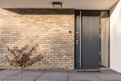 Minimalist clean red brick home exterior with black front door
