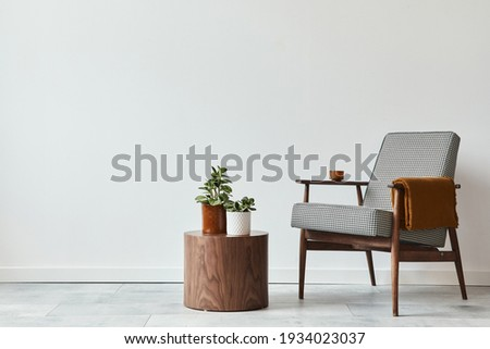 Minimalist composition of living room with design armchair, wooden stool, decoration, plants, copy space and personal accessories in modern home decor. White wall. Template.